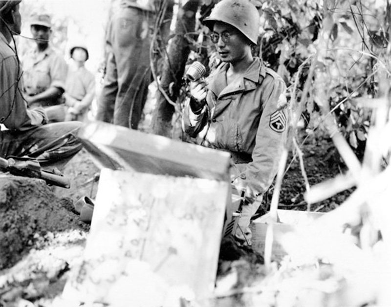 BURMA, 1944: In the jungle near Bhamo, Kenny Yasui, of Los Angeles, uses a loudspeaker to call for Japanese troops to surrender. Yasui earned a Silver Star for capturing 16 Japanese troops on a river island. He swam out to the island with some GIs and, posing as a Japanese colonel, ordered the holdouts into formation and had them turn in their arms. To get back across the river, he had the new POWs pull him on a raft. National Archives photo