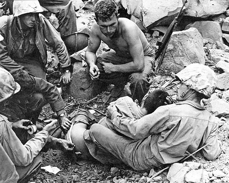 IWO JIMA, March 9, 1945: Tom Miyagi, MIS linguist with the 5th Marine Division, holds a captured Japanese soldier while marines treat the prisoner's wounds. U.S. Marine Corps photo
