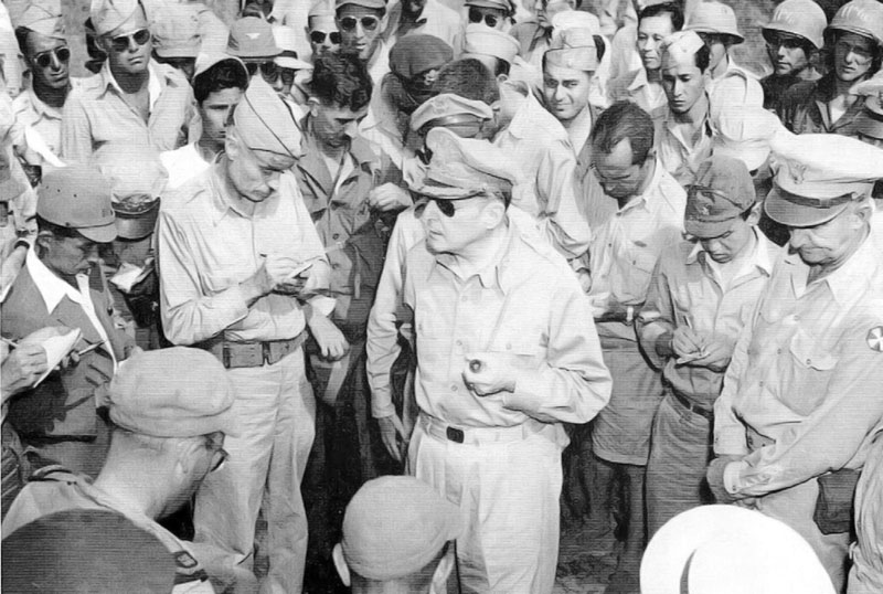 ATSUGI AIR BASE, Japan, August 30, 1945: General Douglas MacArthur addresses U.S. and Japanese reporters after his victorious arrival on Japanese soil. MIS linguist Tom Sakamoto is behind MacArthur, in upper right. (National Archives photo)