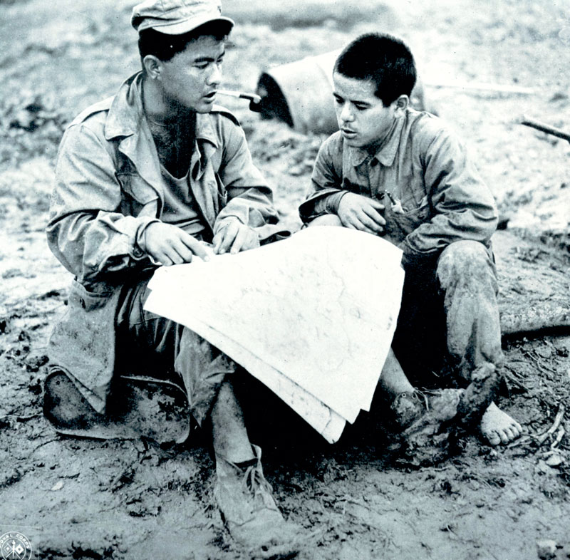 OKINAWA, 1945: Warren Higa, left, of Honolulu, questions a prisoner about Japanese positions. Higa and his brother Takejiro were from Hawaii but went to school on Okinawa. They returned there with the U.S. 96th Infantry Division. U.S. Army Signal Corps photo